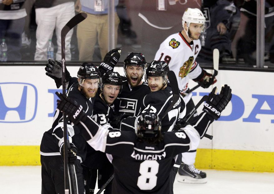 Los Angeles Kings' Jeff Carter (77), Tyler Toffoli (73), Jake Muzzin (6), Dustin Brown (23) and Drew Doughty (8) celebrate a goal by Muzzin as Chicago Blackhawks' Jonathan Toews (19) skates behind them during the first period of Game 4 of the Western Conference finals of the NHL hockey Stanley Cup playoffs on Monday, May 26, 2014, in Los Angeles. (AP Photo/Jae C. Hong)