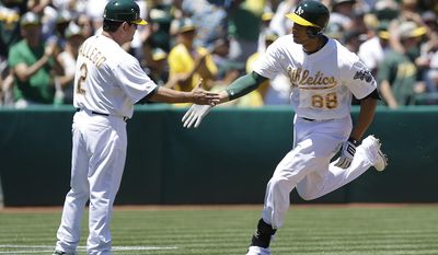 CORRECTS DATE TO 26 -Oakland Athletics' Kyle Blanks, right, is congratulated by third base coach Mike Gallego (2) after hitting a home run off Detroit Tigers' Drew Smyly  in the second inning of a baseball game Monday, May 26, 2014, in Oakland, Calif. (AP Photo/Ben Margot)