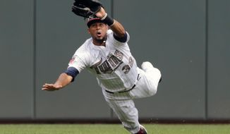 Minnesota Twins' Aaron Hicks dives to catch a shallow fly ball off the bat of Mitch Moreland in the fifth inning on a baseball game Monday, May 26, 2014, in Minneapolis. (AP Photo/Jim Mone)