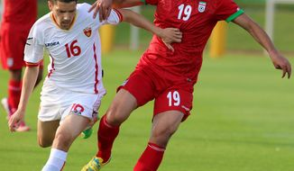 Iran's Hashem Beikzadeh, right, challenges for a ball with Miroie Jovanovic, left, of Montenegro during a friendly soccer match between Iran and Montenegro, in Hartberg, Austria, Monday, May 26, 2014. (AP Photo/Ronald Zak)