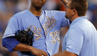 Kansas City Royals starting pitcher Yordano Ventura (30) is checked out by a team trainer before being relieved in the third inning of a baseball game against the Houston Astros at Kauffman Stadium in Kansas City, Mo., Monday, May 26, 2014. Ventura gave up five runs in the first two innings. (AP Photo/Orlin Wagner)