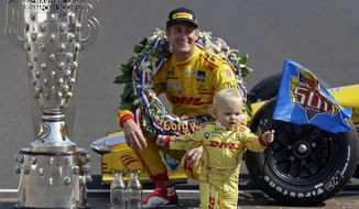 Indianapolis 500 champion Ryan Hunter-Reay watch as his son Ryden walks away with an Indy 500 flag as he poses during the traditional winners photo session on the start/finish line at the Indianapolis Motor Speedway in Indianapolis, Monday, May 26, 2014.  Hunter-Reay won the 98th running of the Indianapolis 500 IndyCar auto race on Sunday. (AP Photo/Michael Conroy)
