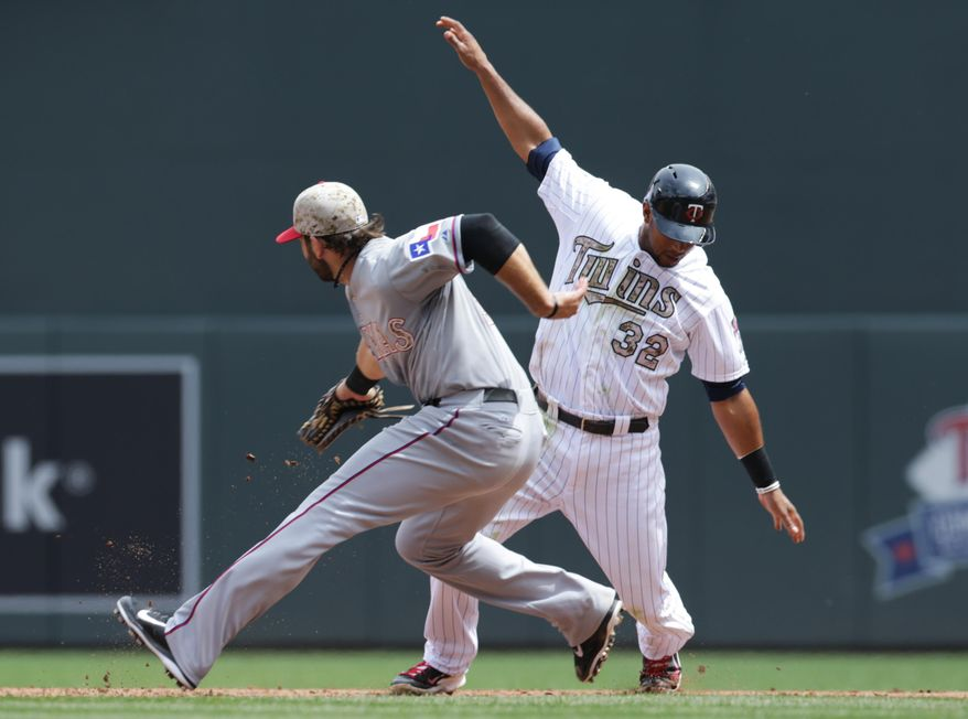 Texas Rangers' first baseman Mitch Moreland, right, tags Minnesota Twins' Aaron Hicks during a failed steal attempt in the fifth inning on a baseball game Monday, May 26, 2014, in Minneapolis. (AP Photo/Jim Mone)
