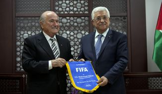 Sepp Blatter, President of FIFA, left, gives a gift with the FIFA logo to Palestinian President Mahmoud Abbas during a meeting at the presidential headquarters on the first day of his regional tour to Jordan, the Palestinian territories and Israel in the West Bank city of Ramallah, Monday, May 26, 2014. During an earlier press conference in Jordan Blatter said that his visit to Ramallah and Israel was to defend football in Palestine and also to defend football in Israel. (AP Photo/Majdi Mohammed)