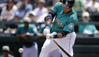 Seattle Mariners' Robinson Cano singles in a run against the Los Angeles Angels in the first inning of a baseball game Monday, May 26, 2014, in Seattle. (AP Photo/Elaine Thompson)