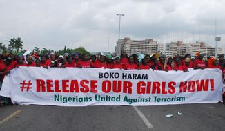 In this Monday, May 26, 2014, photo, the Nigerians United Against Terrorism group attends a demonstration calling on the government to rescue the kidnapped girls of the government secondary school in Chibok, in Abuja, Nigeria.  Nigeria's defense chief said Monday that the military has located nearly 300 school girls abducted by Islamic extremists but cannot use force to free them. (AP Photo/Gbenga Olamikan)