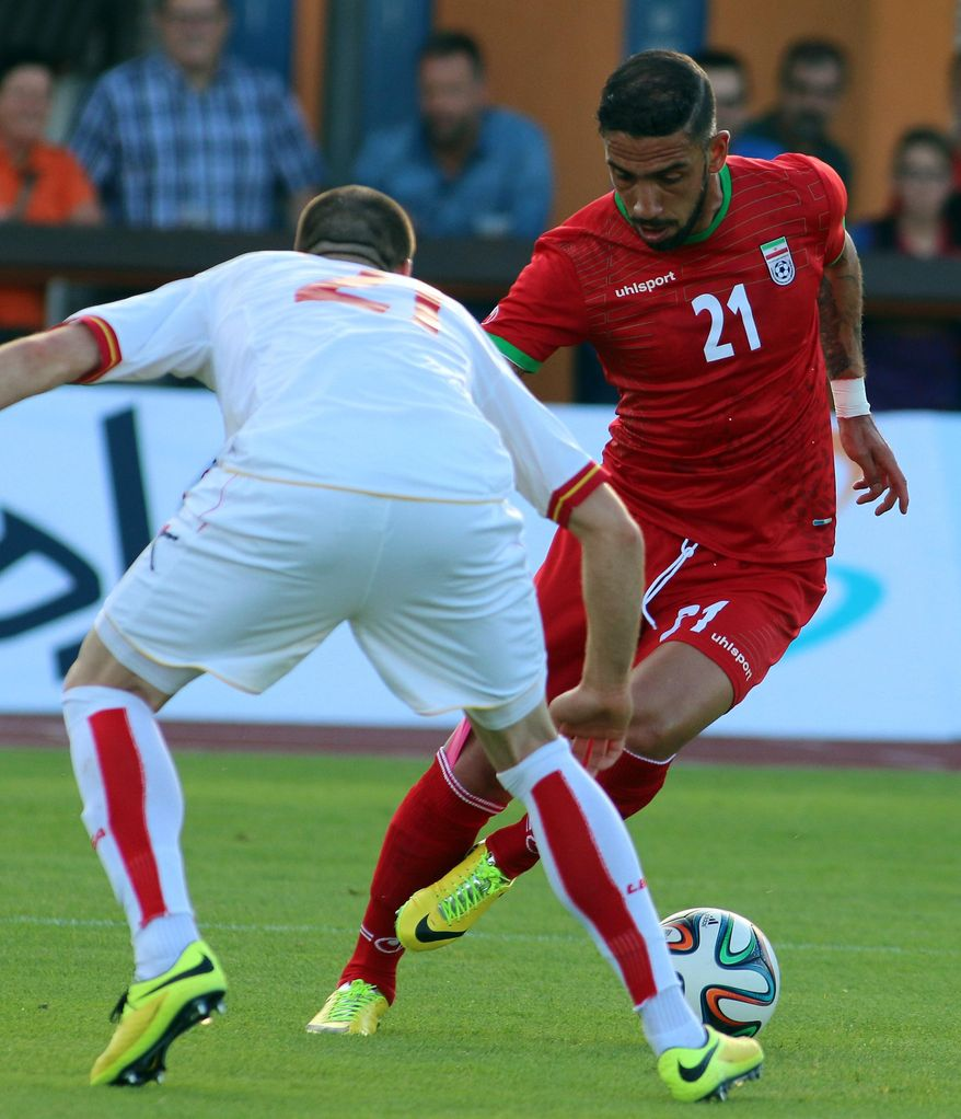 Iran's Ashkan Dejagah, right, challenges for a ball with Sasa Balic, left, of Montenegro during a friendly soccer match between Iran and Montenegro, in Hartberg, Austria, Monday, May 26, 2014. (AP Photo/Ronald Zak)