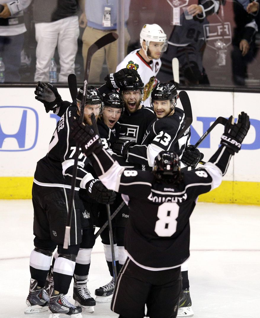 Los Angeles Kings' Jeff Carter (77), Tyler Toffoli (73), Jake Muzzin (6), Dustin Brown (23) and Drew Doughty (8) celebrate a goal by Muzzin as Chicago Blackhawks' Jonathan Toews skates behind them during the first period of Game 4 of the Western Conference finals of the NHL hockey Stanley Cup playoffs on Monday, May 26, 2014, in Los Angeles. (AP Photo/Jae C. Hong)