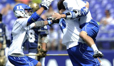 Duke players, left to right, Chad Cohan, Jack Bruckner and Brendan Fowler celebrate after defeating Notre Dame 11-9 in the NCAA college men's championship lacrosse game Monday, May 26, 2014, in Baltimore.(AP Photo/Gail Burton)