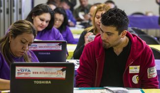 ** FILE ** In this March 31, 2014, file photo, SEIU-UHW worker Kathy Santana, left, assists Ruben Torres, 27, during a health care enrollment event at SEIU-UHW office in Commerce, Calif. (AP Photo/Ringo H.W. Chiu, File)