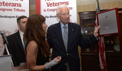 Congressman Ralph Hall, (R-TX), right, holds up his Founding Spirit Award as U.S. Army Sergeant Mary Herrera  looks on during the Honoring Our Veterans and Veterans in Congress program at the Capitol Hill Club on Wednesday, May 21. Khalid Naji-Allah/ Special for The Washington Times