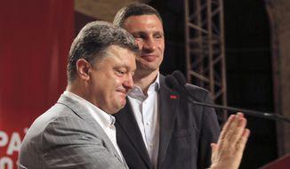 Ukrainian presidential candidate Petro Poroshenko, left, and Vitali Klitschko, pause, during a press conference, in Kiev, Ukraine, Monday, May 26, 2014. (AP Photo/Efrem Lukatsky)