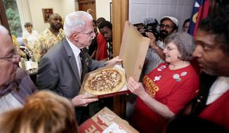 House of Representatives Sergeant-at-Arms Clyde Cook Jr., center, takes two pizzas into activists holding a sit-in at Speaker of the House Thom Tillis' office at the North Carolina General Assembly on Tuesday, May 27, 2014, in Raleigh, N.C. Activists Sandra Howerton, center, 71, of Wilson, and the Rev. William Barber II, right, try to enter the room but are turned away. (AP Photo/The News & Observer, Corey Lowenstein)