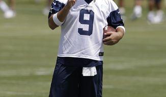 Dallas Cowboys quarterback Tony Romo watches as the team runs drills during an NFL football organized team activity, Tuesday, May 27, 2014, in Irving, Texas. (AP Photo/Tony Gutierrez)