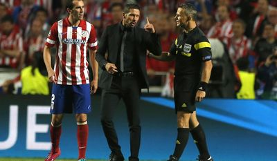 Atletico's coach Diego Simeone, centre, talks with referee Bjorn Kuipers, during the Champions League final soccer match between Atletico Madrid and Real Madrid in Lisbon, Portugal, Saturday, May 24, 2014. (AP Photo/Andres Kudacki)