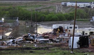 Debris is scattered Tuesday morning, May 27, 2014, after a tornado in Watford City, N.D. Authorities say at least eight trailers were destroyed Monday evening when the twister tore through a camp where oil field workers stay. Nine people were injured, including a 15-year-old girl critically. (AP Photo/Josh Wood)