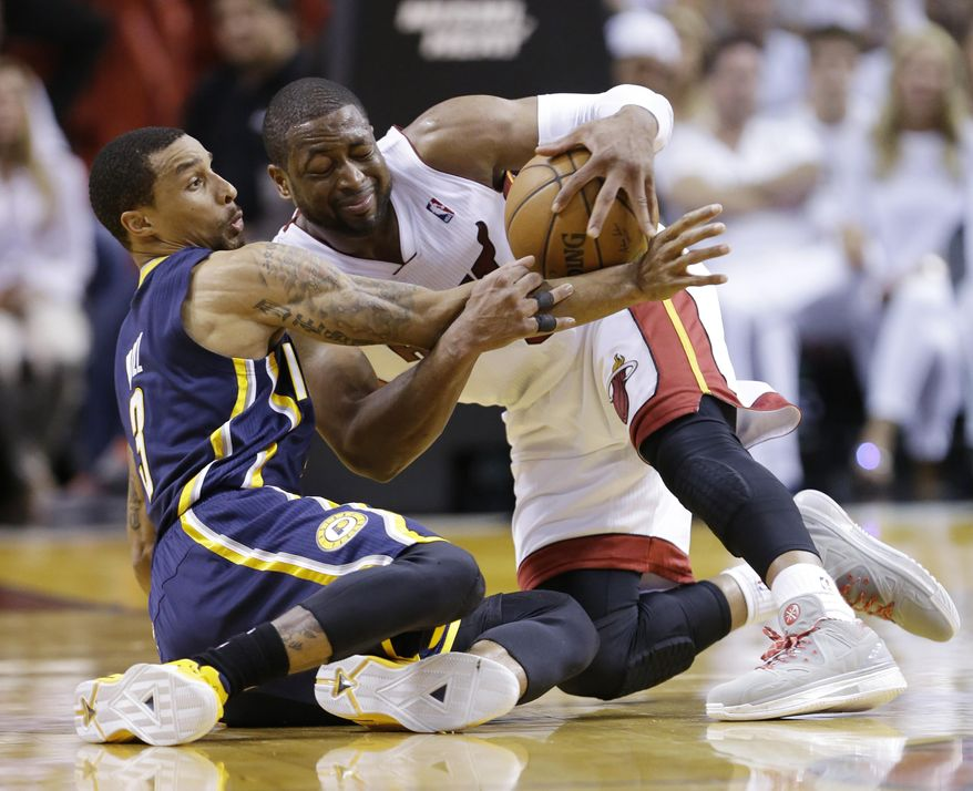 Indiana Pacers guard George Hill (3) and Miami Heat guard Dwyane Wade (3), fight over a loose ball during the first half of Game 4 in the NBA basketball Eastern Conference finals playoff series, Monday, May 26, 2014, in Miami. (AP Photo/Wilfredo Lee)