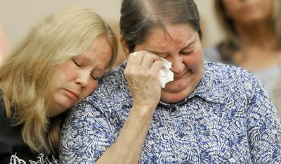 Dustyn Frolka's aunt Lisa Frolka, left, comforts his mother Eileen Hincka before Samantha Grigg is sentenced in Clinton County Circuit Court Tuesday, May 27, 2014,in St. John's Mich. Grigg, an 18-year-old high school senior who drove a vehicle involved in the death Michigan State University student Dustyn Frolka, 19, was sentenced Tuesday to 6 to 15 years in prison for manslaughter and unarmed robbery. (AP Photo/The State Journal, Greg DeRuiter)  NO SALES