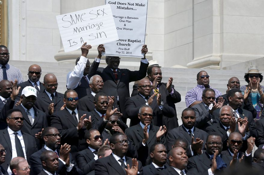 Some of the more than 200 Arkansas pastors opposed to same-sex marriage applaud at a rally on the steps of the Arkansas State Capitol in Little Rock in this May 27, 2014, file photo. (Associated Press) ** FILE **