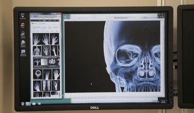 This photo taken on May 19, 2014,  shows a doctor's station featuring touch-screen monitors in one of Sparrow Hospital's new surgical center operating rooms in Lansing, Mich. Sparrow Health System has more than doubled the size of its surgical center in a $15 million expansion at the hospital. (AP Photo/The State Journal, Al Goldis)  NO SALES
