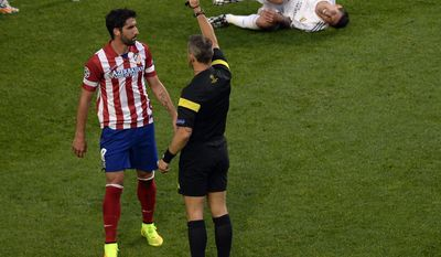 Atletico's Raul Garcia, left, gets the yellow card by referee Bjorn Kuipers during the Champions League final soccer match between Atletico Madrid and Real Madrid in Lisbon, Portugal, Saturday, May 24, 2014. (AP Photo/Paulo Duarte)