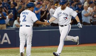 Toronto Blue Jays Adam Lind celebrates a home run with third base coach Luis Rivera, left, during the fifth inning of a baseball game in Toronto on Tuesday, May 27, 2014. (AP Photo/The Canadian Press, Aaron Vincent Elkaim)