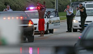 Deputies pulled over a car and took people into custody following shooting near a hotel in Clearwater, Fla., that brought out a large police response and caused the beach to be closed to incoming traffic Monday, May 26, 2014. (AP Photo/The Tampa Bay Times, Jim Damaske)