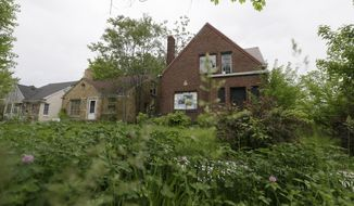 Grass and weeds grow in front of two vacant homes in Detroit, Tuesday, May 27, 2014. Removing blighted residential properties, lots and vacant commercial structures that have plagued Detroit neighborhoods for decades would cost $850 million, a task force said Tuesday. The study by the Detroit Blight Removal Task Force is part of efforts announced last year by the administration of President Barack Obama to help Detroit, which is trying to work through the largest municipal bankruptcy in U.S. history. (AP Photo/Carlos Osorio)