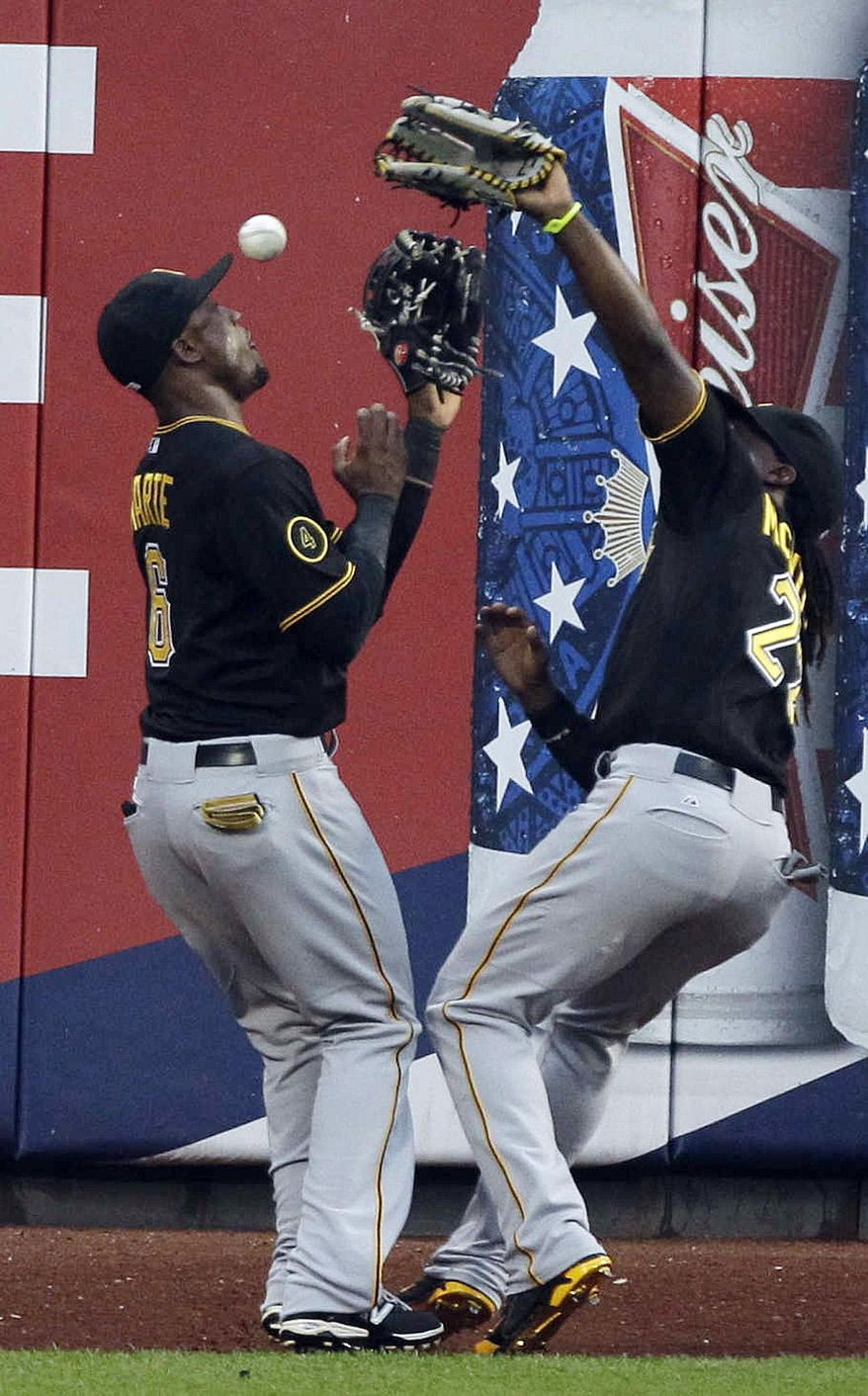 Pittsburgh Pirates left fielder Starling Marte (6) and Andrew McCutchen collide and lose control of a ball hit by New York Mets' Daniel Murphy during the first inning of a baseball game Tuesday, May 27, 2014, in New York. (AP Photo/Frank Franklin II)