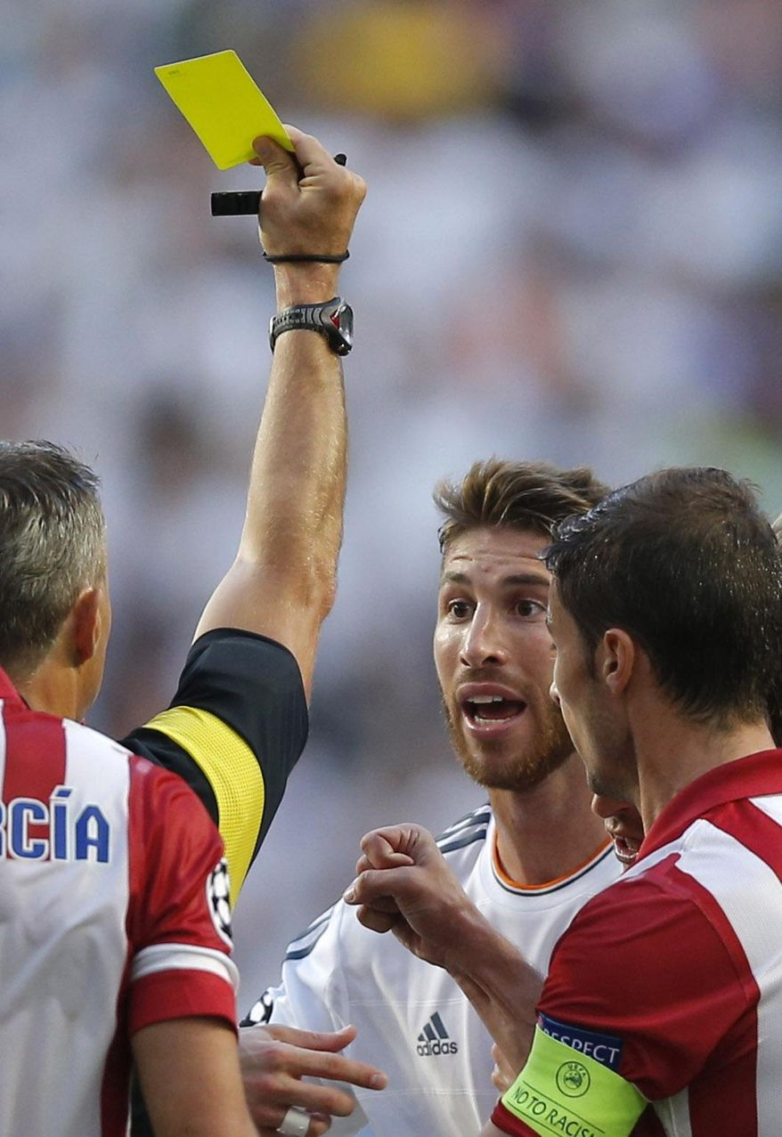 Real's Sergio Ramos, centre is given a yellow card by referee Bjorn Kuipers,  during the Champions League final soccer match between Atletico de Madrid and Real Madrid, at the Luz stadium, in Lisbon, Portugal, Saturday, May 24, 2014. (AP Photo/Daniel Ochoa de Olza)