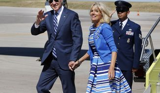 Vice President Joe Biden, left, walks from Air Force Two with his wife Jill Biden, upon arrival at Denver International Airport, Tuesday May 27, 2014, in Denver. Biden is in Colorado for a fundraiser with Sen. Mark Udall, and to attend Wednesday's Air Force Academy graduation ceremony. (AP Photo/Brennan Linsley)