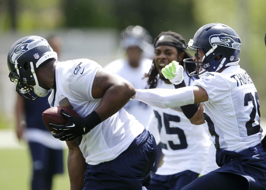 Seattle Seahawks free safety Earl Thomas, right, celebrates with defensive end Greg Scruggs, left, and cornerback Richard Sherman, center, after Scruggs made an interception in a practice drill during an NFL football organized team activity, Tuesday, May 27, 2014, in Renton, Wash. (AP Photo/Ted S. Warren)