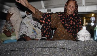 A family member of a pregnant woman who was stoned to death by her own family wails over her dead body in an ambulance at a local hospital in Lahore, Pakistan, Tuesday, May 27, 2014. Nearly 20 members of the woman's family, including her father and brothers, attacked her and her husband with batons and bricks in broad daylight before a crowd of onlookers in front of the high court of Lahore, police investigator Rana Mujahid said. (AP Photo/K.M. Chaudary)