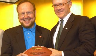FILE - In this July 31, 2003 file photo, Tampa Bay Buccaneers owner Malcolm Glazer, left, and his New York Jets counterpart Robert Woody Johnson smile as they hold a football together during a press conference at Tokyo Dome hotel in Tokyo. Glazer, the self-made billionaire who owned the NFL's Tampa Bay Buccaneers and English soccer's Manchester United, has died.  He was 85. The Bucs said Glazer died Wednesday, May 28, 2014. (AP Photo/Katsumi Kasahara, File)