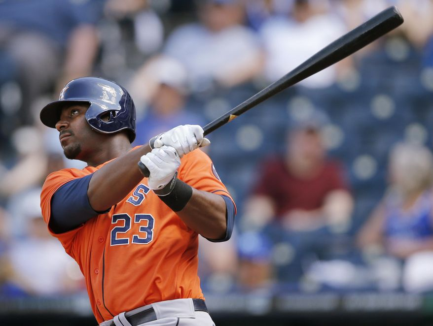 Houston Astros' Chris Carter follows through on a three-run home run off Kansas City Royals relief pitcher Louis Coleman during the sixth inning of a baseball game at Kauffman Stadium in Kansas City, Mo., Wednesday, May 28, 2014. (AP Photo/Orlin Wagner)
