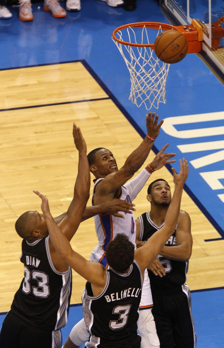Oklahoma City Thunder guard Russell Westbrook (0) takes a shot against San Antonio Spurs forward Boris Diaw (33), guard Marco Belinelli (3) and guard Cory Joseph (5) in the second half of Game 4 of the Western Conference finals NBA basketball playoff series in Oklahoma City, Tuesday, May 27, 2014. (AP Photo/Garett Fisbeck)