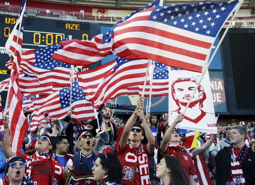 Fans wave American flags before the start of an international friendly soccer match between the United States and Azerbaijan on Tuesday, May 27, 2014, in San Francisco. (AP Photo/Marcio Jose Sanchez)
