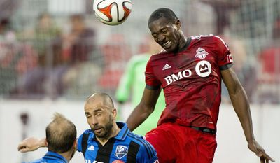 Toronto FC defender Doneil Henry, right, heads the ball past Montreal Impact's Marco Di Vaio, center and Justin Mapp during the first half in the first leg of the Canadian Championship soccer final, in Toronto on Wednesday, May 28, 2014. (AP Photo/The Canadian Press, Nathan Denette)