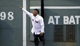 Former Boston Red Sox's Manny Ramirez runs out from the Green Monster door in left field at Fenway Park prior to a baseball game against the Atlanta Braves in Boston, Wednesday, May 28, 2014. The Red Sox honored the 2004 World Series team prior to the game. (AP Photo/Elise Amendola)