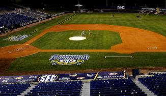 In this May 24, 2014 photo, ground crew members spray the field after a game at the Southeastern Conference NCAA college baseball tournament in Hoover, Ala. (AP Photo/Butch Dill)