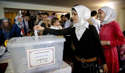 A Syrian woman who lives in Iran casts her ballot for her country's presidential election at the Syrian Embassy in Tehran, Iran, Wednesday, May 28, 2014, as expat voting started ahead of Syria's June 3 presidential election - a vote highly contentious amid the civil war but one that is widely expected to give the Syrian president a third seven-year term in office. (AP Photo/Ebrahim Noroozi)