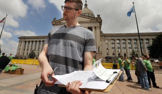 David Barham, of Tulsa, asks for signatures on a petition during a medical marijuana rally at the State Capitol on Wednesday, May 28, 2014 in Oklahoma City, Okla. The rally is formal launch of a signature drive to get a medical marijuana measure on a statewide ballot.  (AP Photo/The Oklahoman, Steve Sisney)