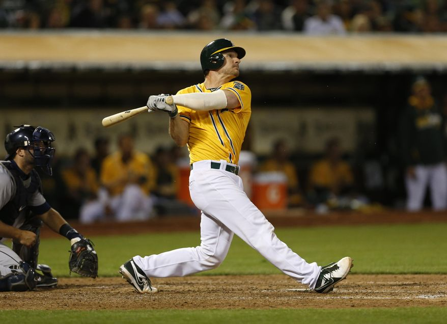 Oakland Athletics catcher John Jaso hits a two-run home run during the fourth inning of a baseball game against the Detroit Tigers, Tuesday, May 27, 2014, in Oakland, Calif. (AP Photo/Beck Diefenbach)