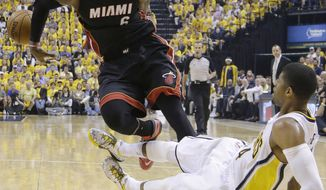 Miami Heat forward LeBron James (6) loses the ball as Indiana Pacers' Paul George goes down during the first half of Game 5 of the NBA basketball Eastern Conference finals in Indianapolis, Wednesday, May 28, 2014. (AP Photo/Michael Conroy)