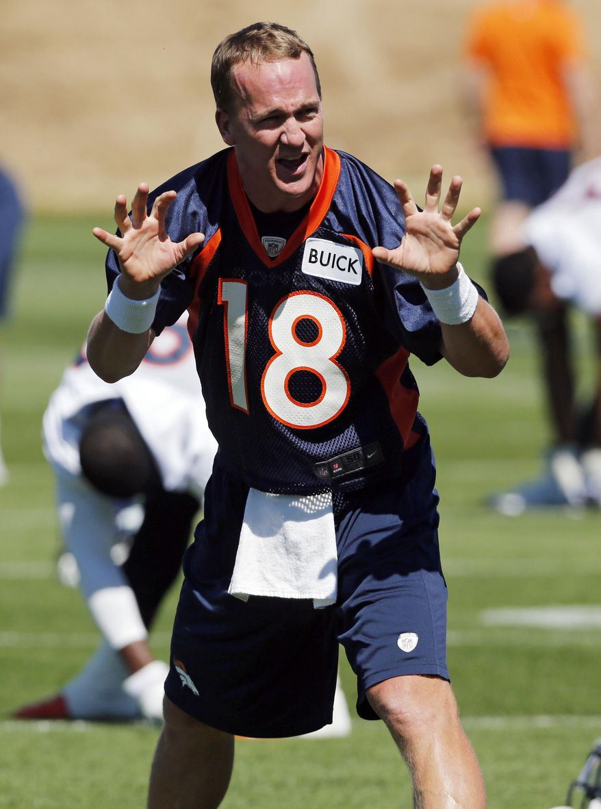 Denver Broncos Peyton Manning talks to teammates as they warmup during an NFL football organized team practice at the Broncos training facility in Englewood, Colo., on Wednesday, May 28, 2014. (AP Photo/Ed Andrieski)