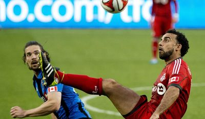 Toronto FC forward Dwayne De Rosario, right, eyes the ball against Montreal Impact defender Heath Pearce, left, during the first half in the first leg of the Canadian Championship soccer final, in Toronto on Wednesday, May 28, 2014. (AP Photo/The Canadian Press, Nathan Denette)