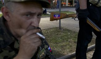 A sticker with Donetsk people's republic colors is seen on the hunting rifle of a local man who came to a check point on a road leading to the airport, in Donetsk, Ukraine, on Tuesday, May 27, 2014.  The eastern city of Donetsk was in turmoil Tuesday a day after government forces used fighter jets to stop pro-Russian militia from taking over the airport. Dozens were reported killed and the mayor went on television to urge residents to stay indoors. (AP Photo/Ivan Sekretarev)