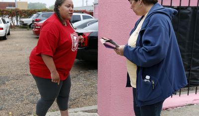 In this April 15, 2013 photo, Laurie Bertram Roberts, left, president of Mississippi's chapter of the National Organization for Women, confronts an abortion opponent who was blocking the driveway to the Jackson Women's Health Organization's clinic in Jackson, Miss. Roberts has volunteered as an escort at the clinic and said if facilities close, women would likely try to end their own pregnancies in potentially dangerous ways. (AP Photo/Rogelio V. Solis)