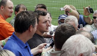 Writers crowd around Cleveland Browns quarterback Johnny Manziel, center, after an organized team activitiy at the NFL football team's facility in Berea, Ohio Wednesday, May 28, 2014. (AP Photo/Mark Duncan)