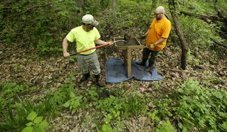 Wapsi Valley Archaeology Inc. workers Pat Hashman, left, and Owen Reese dig for artifacts in a World War I training trench at the Iowa National Guard Base at Camp Dodge, Wednesday, May 28, 2014, in Johnston, Iowa. Excavation is underway at the camp as part of an archaeological dig to learn more about trench complexes built for training soldiers in World War I.  Camp Dodge, originally established in 1909, was one of 16 U.S. Army installations across the country to be transformed for training from 1917 to 1919. (AP Photo/Charlie Neibergall)